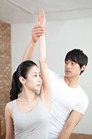 Male Instructor Helping Woman With Pose