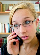 Teenager talking on phone surprised
