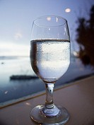 Glass of water in front of the ocean at sunset in Morro Bay, California, United States