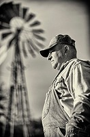 Portrait of American Farmer Vintage Style Black and White with Ranch Windmill in Background