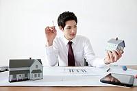 Businessman holding model house at desk