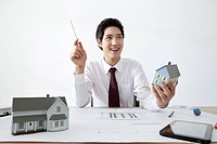 Businessman holding model house at desk