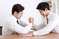 Businessmen doing arm_wrestling in the office
