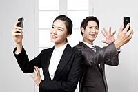 Businesswoman and businessman using smart phones