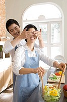 Woman cooking in kitchen and man covering her eyes