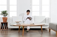 Young man reading a magazine on sofa at home