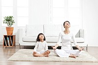 Mother and daughter sitting on carpet
