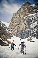 Two male backcountry skiers bootpack up a steep spring couloir. 3/4 couloir, Moraine Lake, Banff National Park, Alberta, Canada
