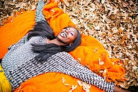 Portrait of a young women smiling outside playing with a pile of leaves during fall.