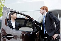 Businessman and businesswoman standing by a car