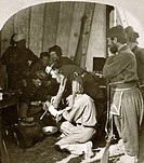 Military field hospital, US Civil War. This stereographic image shows soldiers in a field hospital with amputation tools and a patient with an injured...