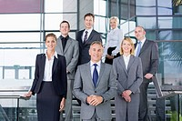 Portrait of smiling business people in suits standing on steps