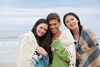 Portrait of smiling young women wrapped in blankets on beach