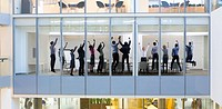 View of business people celebrating in conference room from outdoors
