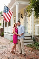 Caucasian couple hugging near porch