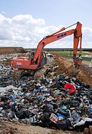 Landfill site. Digger covering waste at a landfill site with soil. Photographed in France.