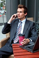 young caucasian businessman using his laptop in cafe _ drinking