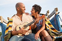 Man playing ukulele for wife on back of truck