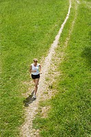 Germany, Munich, Mid adult woman jogging on grassy land