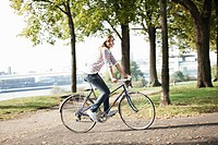 Germany, Cologne, Young woman on bicycle, smiling, portrait