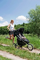 Germany, Munich, Mother jogging with baby boy in pram