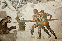 The mosaic depicting two men with long hunting spears struggling with a tiger. The men are wearing sleeveless tunics and large shawls.