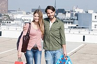 Germany, Cologne, Young couple with shopping bags, smiling, portrait