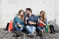 Germany, Cologne, Young man and woman with ice cream and shopping bags, smiling