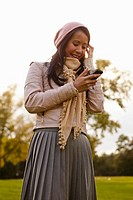 Germany, Cologne, Young woman with cell phone in park, smiling