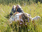 Woman lies in mountain meadow, on leather pillow