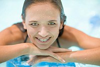 Teenage girl in braces relaxing in pool