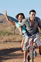 Couple riding bicycle on dirt road