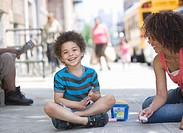 Mother and son drawing on sidewalk with chalk