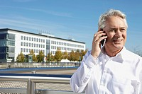 Germany, Bavaria, Munich, Businessman talking on phone, smiling