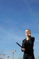 Germany, Bavaria, Munich, Businesswoman talking on cell phone, smiling