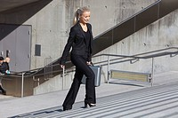 Germany, Bavaria, Munich, Businesswoman walking on stairs with briefcase, smiling