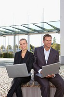 Germany, Bavaria, Munich, Business people using laptop, smiling