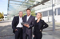 Germany, Bavaria, Munich, Business people using digital tablet, smiling, portrait