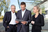 Germany, Bavaria, Munich, Business people using digital tablet, smiling