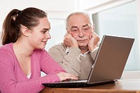 Young woman and frustrated senior man using laptop