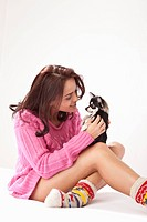 Young woman snuggling with chihuahua on bed