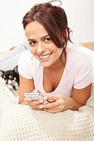 Young woman on phone with chihuahua, smiling, portrait