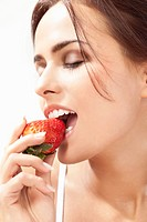 Young woman eating strawberry, close up