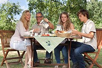 Family of four having breakfast at garden table