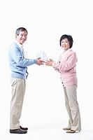 An elderly man giving the gift for an elderly woman