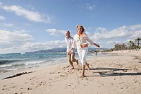Spain, Mallorca, Senior couple running along beach, smiling