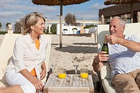 Spain, Mallorca, Senior couple with drink at beach