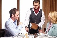 Waiter serving business people in cafe