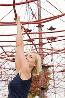 Germany, North Rhine_Westphalia, Duesseldorf, Young woman hanging on climbing frame in playground