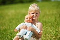 Germany, Bavaria, Girl with baby doll in grass, smiling, portrait